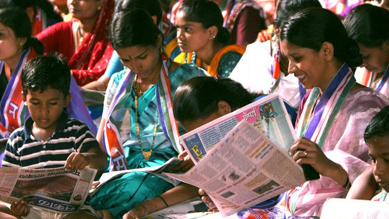Indiska väljare läser tidningar under ett valmöte. Foto: Al Jazeera English (CC BY-SA 2.0).