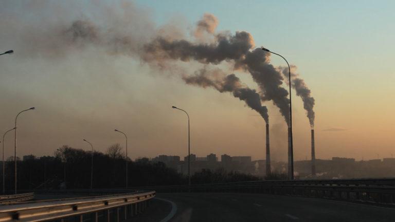 Utsläpp från skorstenar i soluppgång.