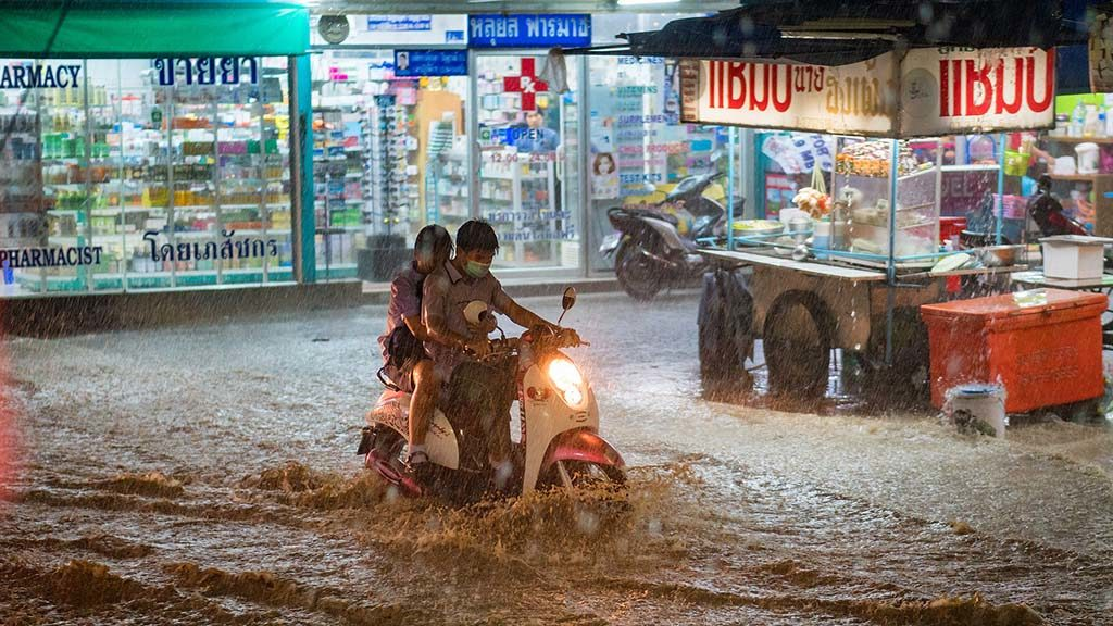 Två ungdomar åker moped genom översvämningar.