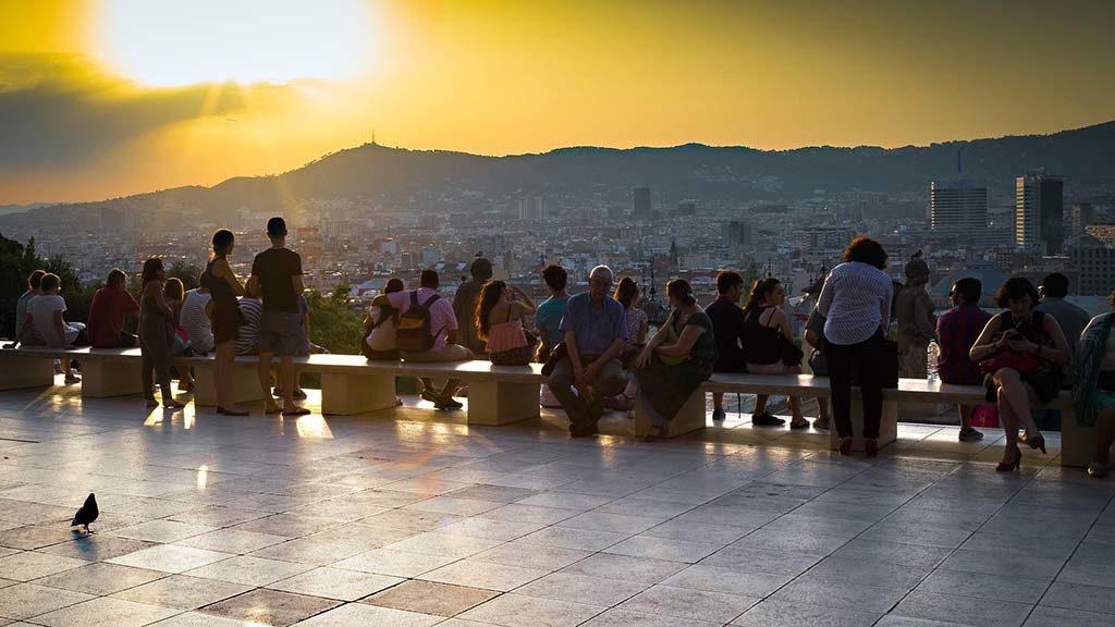 Turister tittar på solnedgången över Barcelona.