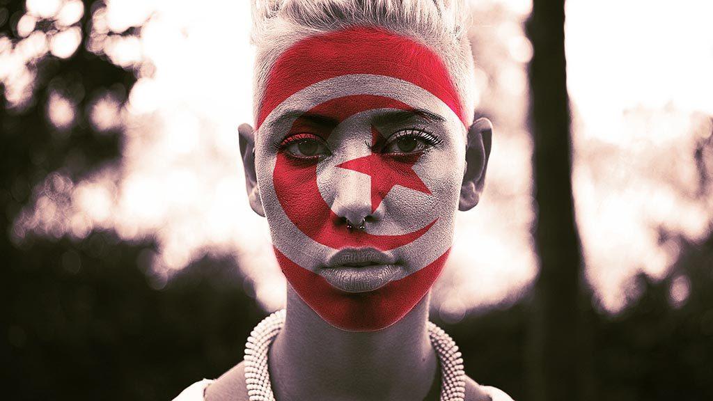 Kvinna med Tunisiens flagga målad i ansiktet.