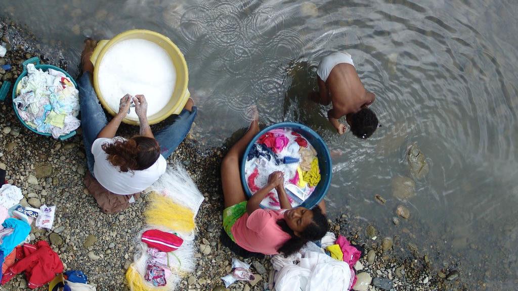 Några kvinnor tvättar kläder i en flod och ett barn badar.