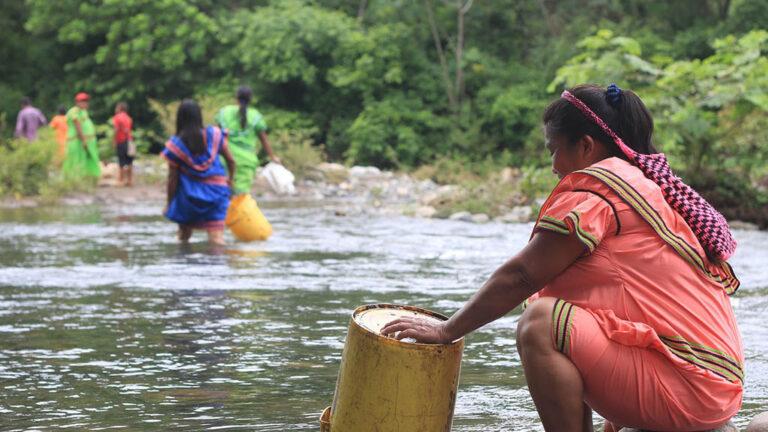 Kvinnor tvättar kläder i en flod.
