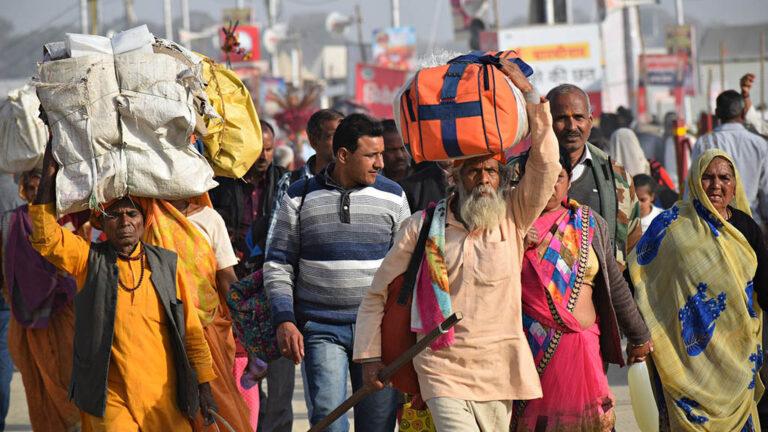 Människor i Indien som förlorat sina jobb vandrar hemåt
