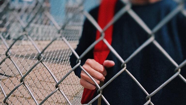 Ungdom med ryggsäck vid staket